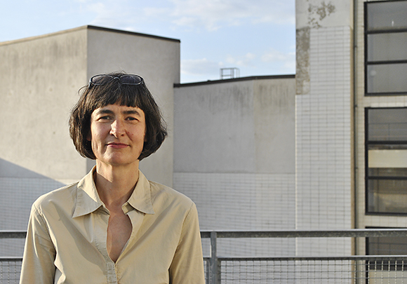 Ein Portrait von Andrea Jaschinski mit Hauswand und Himmel im Hintergrund